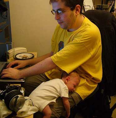 geek with baby sleeping on his knee